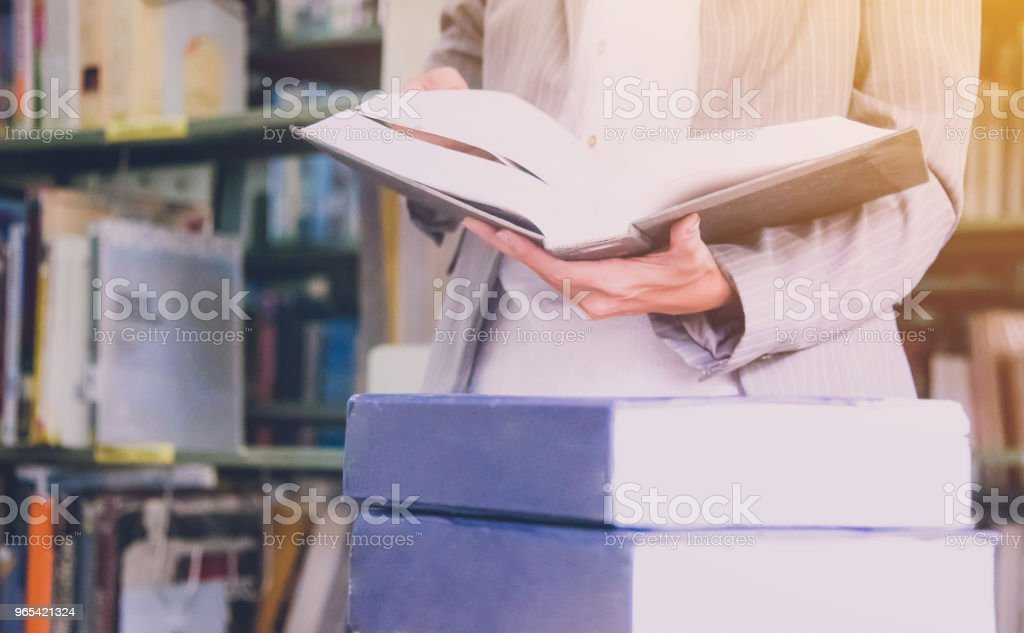Teacher holding text book with soft light morning in library background royalty-free stock photo