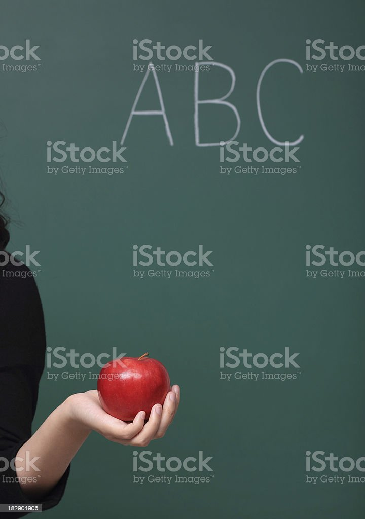 \'An anonymous female teacher holds a bright, red apple in front of a...