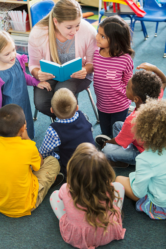 A preschooler teacher in the classroom reading to her class.  The multiracial children are sitting on the floor looking up at her.  She is talking to a little girl of Pacific Islander ethnicity who is kneeling beside her.