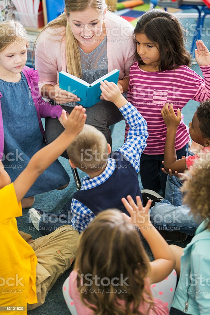 Teacher in class with multiracial group of preschoolers stock photo