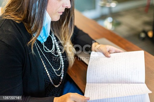868148002 istock photo Teacher in Classroom Grading Homework with Face Mask Draped Over Ear 1257207161