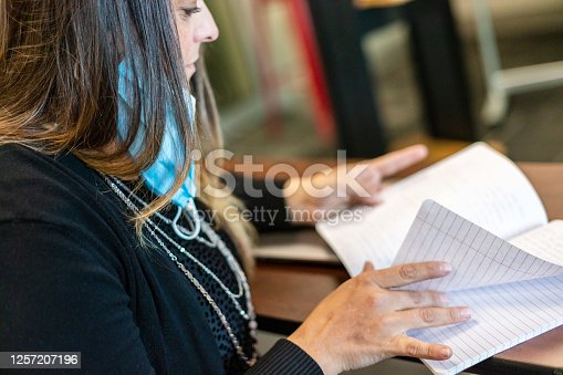 868148002 istock photo Teacher in Classroom Grading Homework with Face Mask Draped Over Ear 1257207196