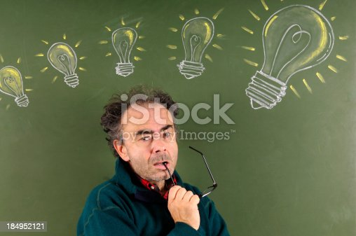 184960675 istock photo Teacher in Front Of Blackboard W Sketched Light Bulbs 184952121