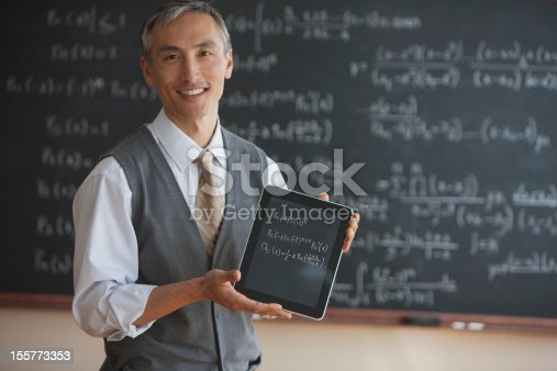 istock Teacher in front of blackboard with electronic tablet 155773353