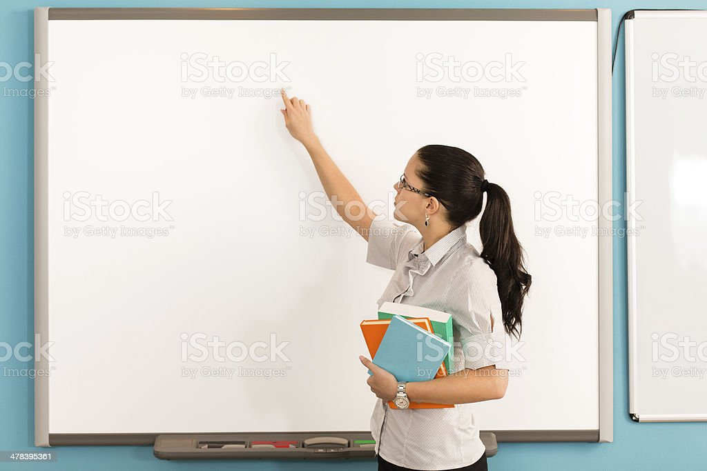 Teacher in front of whiteboard in the classroom stock photo