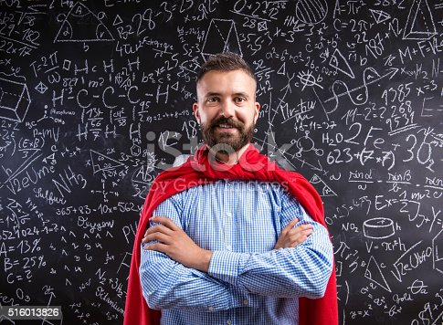 istock Teacher in red cape against big blackboard with mathematical sym 516013826