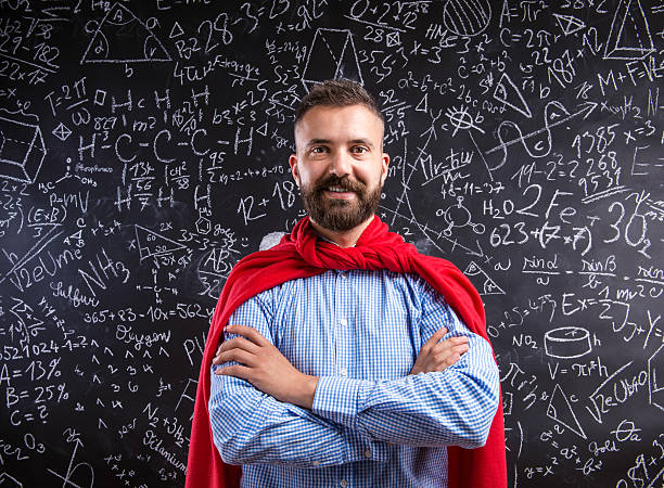 Teacher in red cape against big blackboard with mathematical sym stock photo