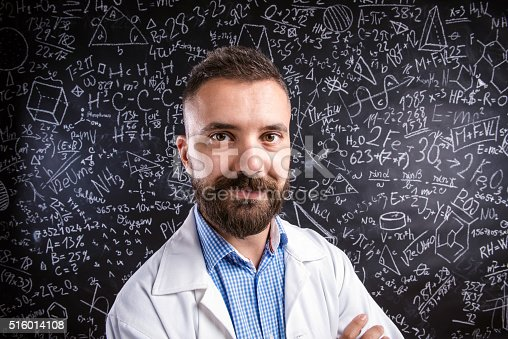 istock Teacher in white coat against big blackboard with mathematical s 516014108