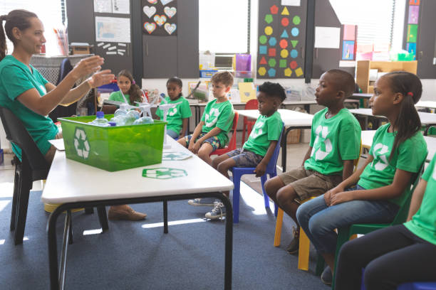 Teacher interacting with school kids about green energy and recycle stock photo