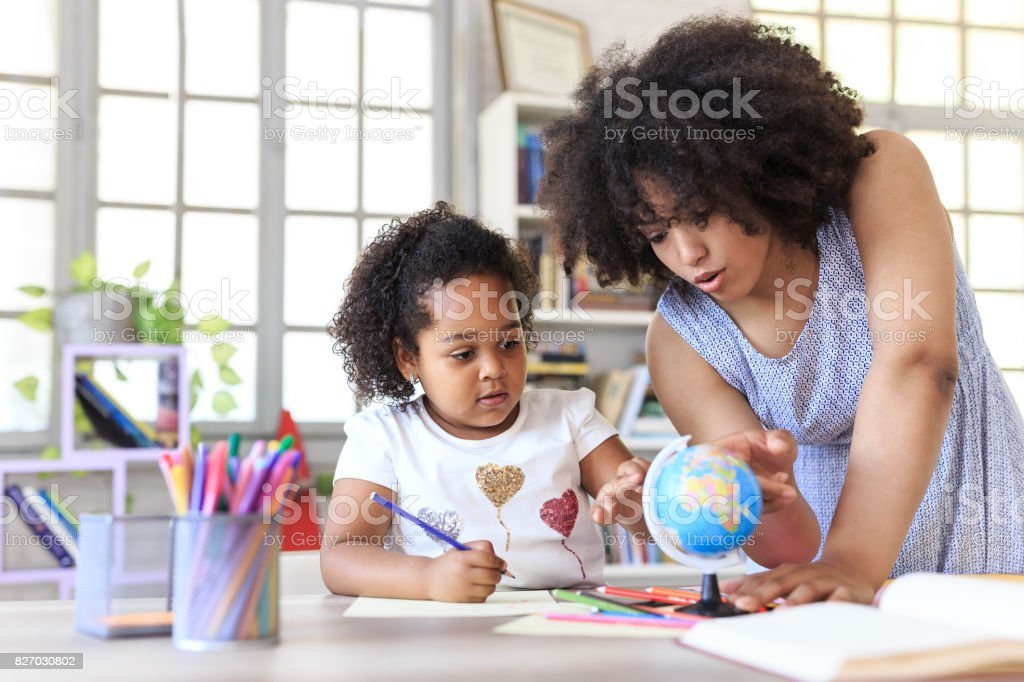 Teacher learning little girl Young teacher learning little girl to use a globe. Achievement Stock Photo