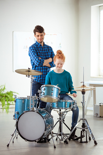 Teacher Looking At Drummer Practicing In Classroom Stock Photo - Download Image Now