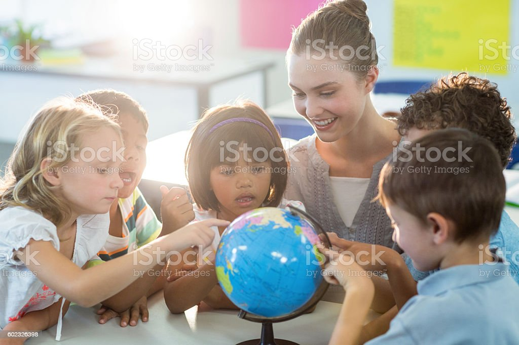 Teacher looking at schoolchildren touching globe stock photo