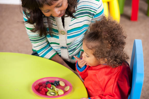 Lehrer, Kleinkind, die Früchte zu essen, am Tisch zu betrachten – Foto
