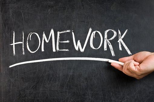 Teacher male hand with white chalk underlining handwritten homework text on dirty blackboard