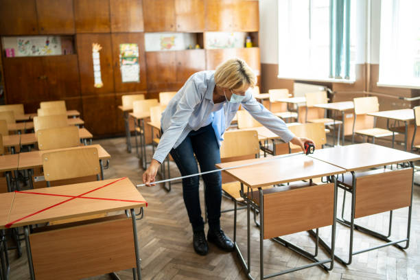 covid-19. teacher marks empty places in the classroom - social distancing stock pictures, royalty-free photos & images
