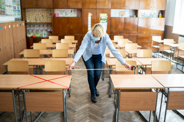 COVID-19. Teacher marks empty places in the classroom