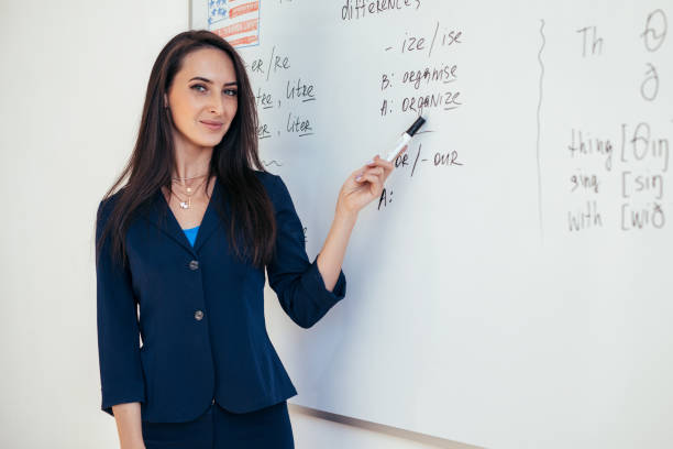 Teacher near whiteboard explains the rules. Learn foreign language. stock photo