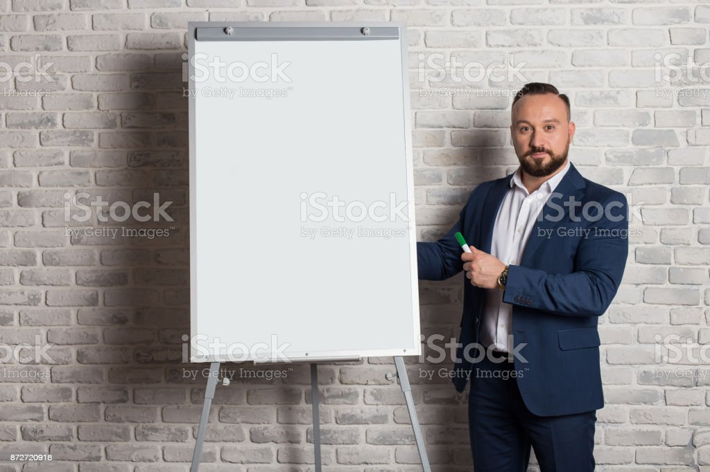 A teacher or business coach is standing next to a whiteboard for writing text. Board with copy space, isolated on white background. Handsome businessman standing at the whiteboard. Brick background stock photo
