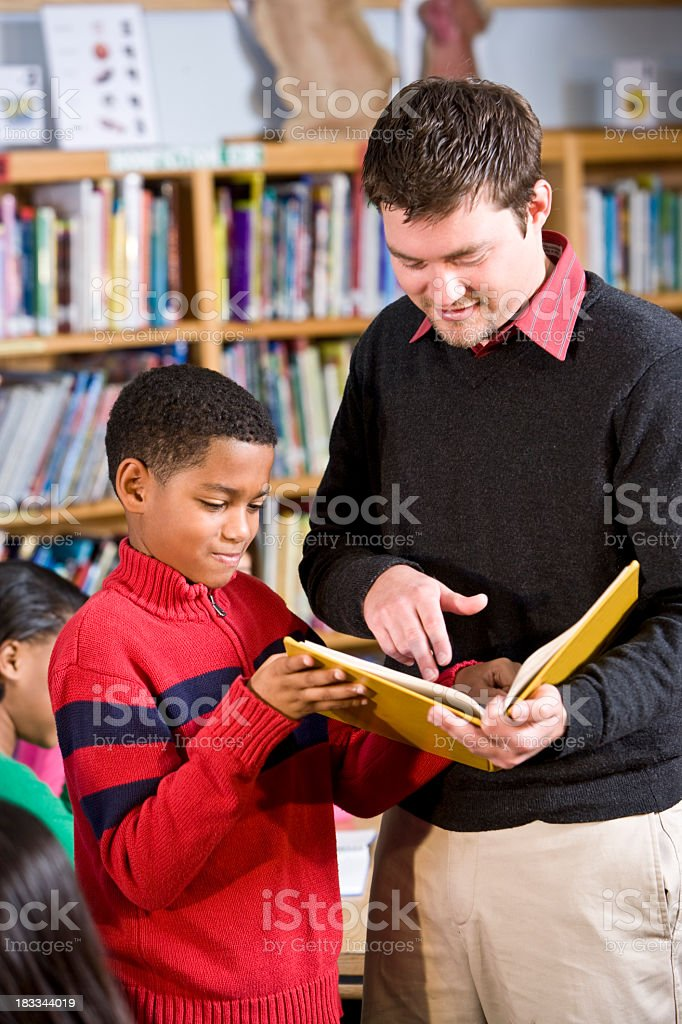 Teacher or librarian helping African American boy in library royalty-free stock photo