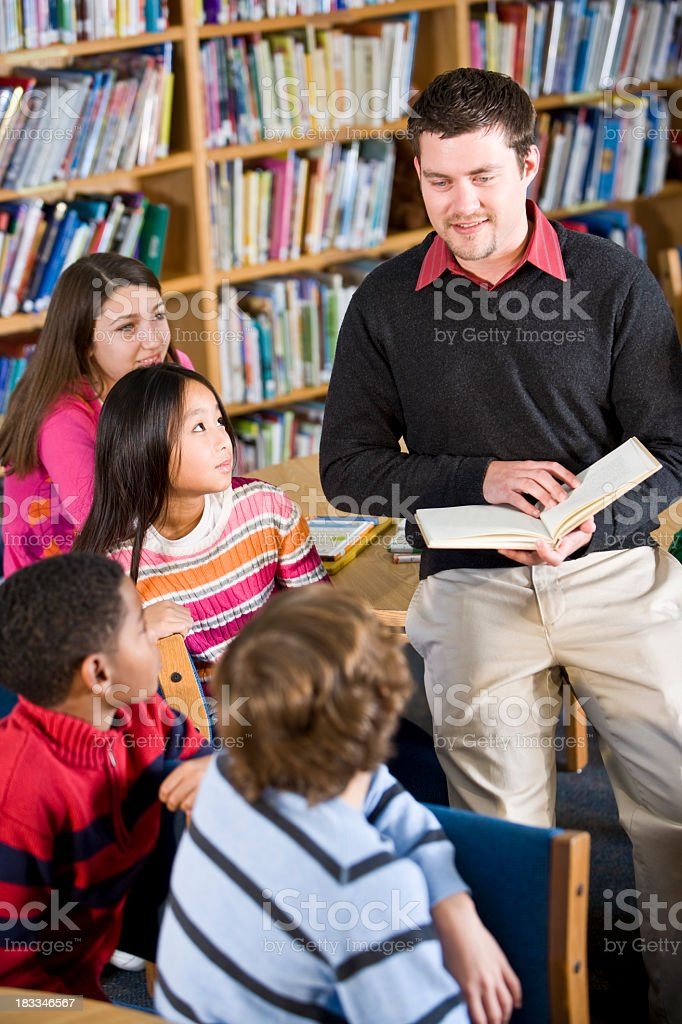 Teacher or librarian reading to group of children royalty-free stock photo