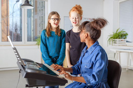 Teacher Playing Piano While Students Singing Stock Photo - Download Image Now