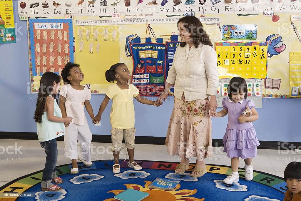 Teacher playing with children (2-5), smiling royalty-free stock photo