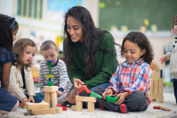 Teacher playing with students A young beautiful teacher is playing with her students. She has a giant smile on her face while she holds a block in her hand. preschool student stock pictures, royalty-free photos & images