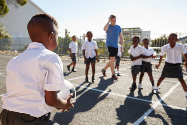 Teacher plays football with young kids in school playground stock photo