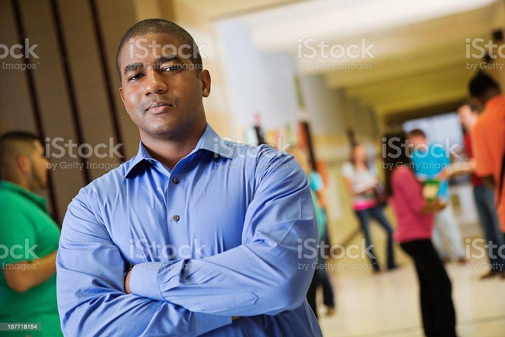 Teacher posing in busy high school hallway between classes stock photo