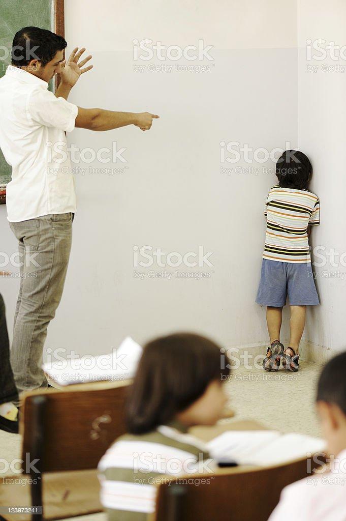 Teacher punishing child at classroom, putting him in corner royalty-free stock photo