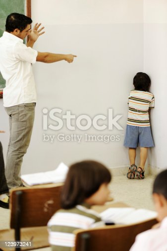 istock Teacher punishing child at classroom, putting him in corner 123973241