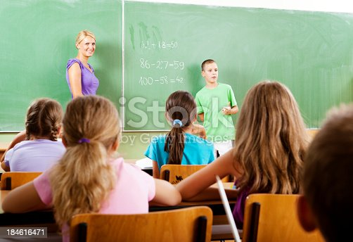 istock Teacher questioning little boy student at the blackboard 184616471