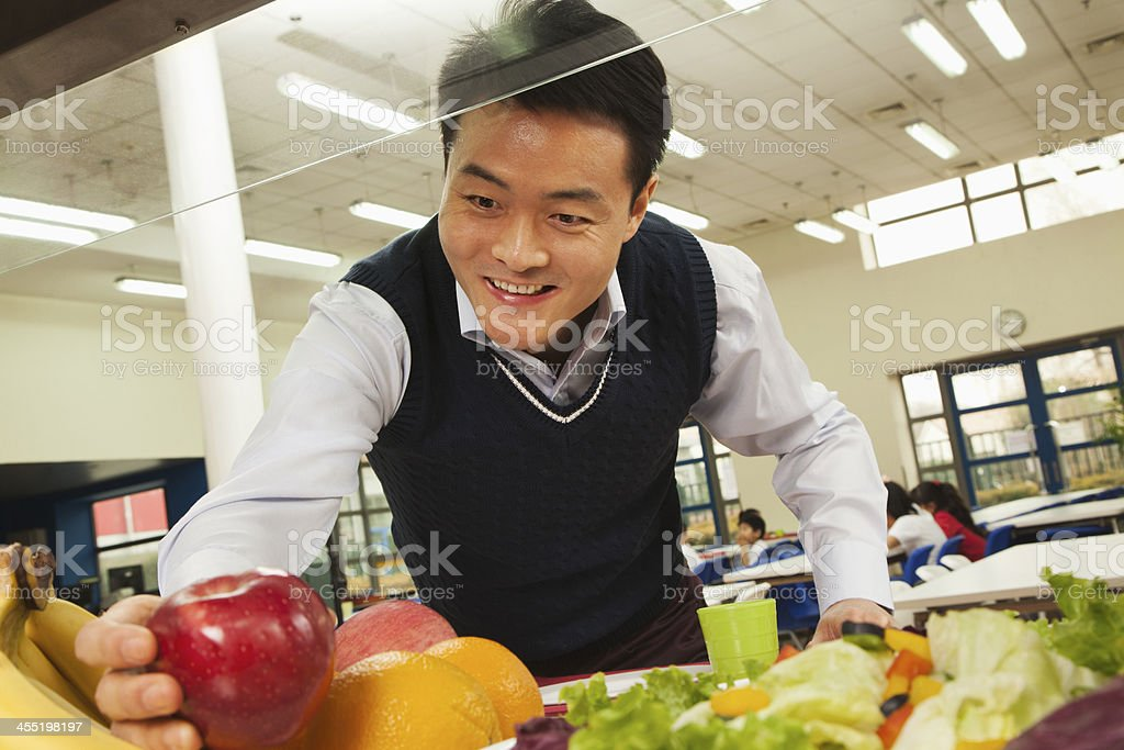 Teacher reaching for healthy food in school cafeteria stock photo