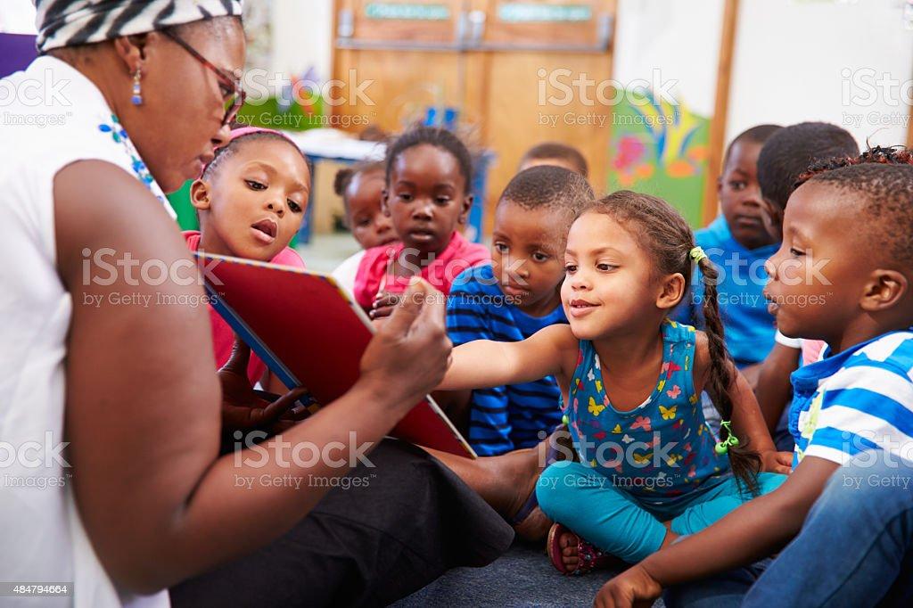 Insegnante lettura di un libro con una classe di scuola materna bambini - foto stock