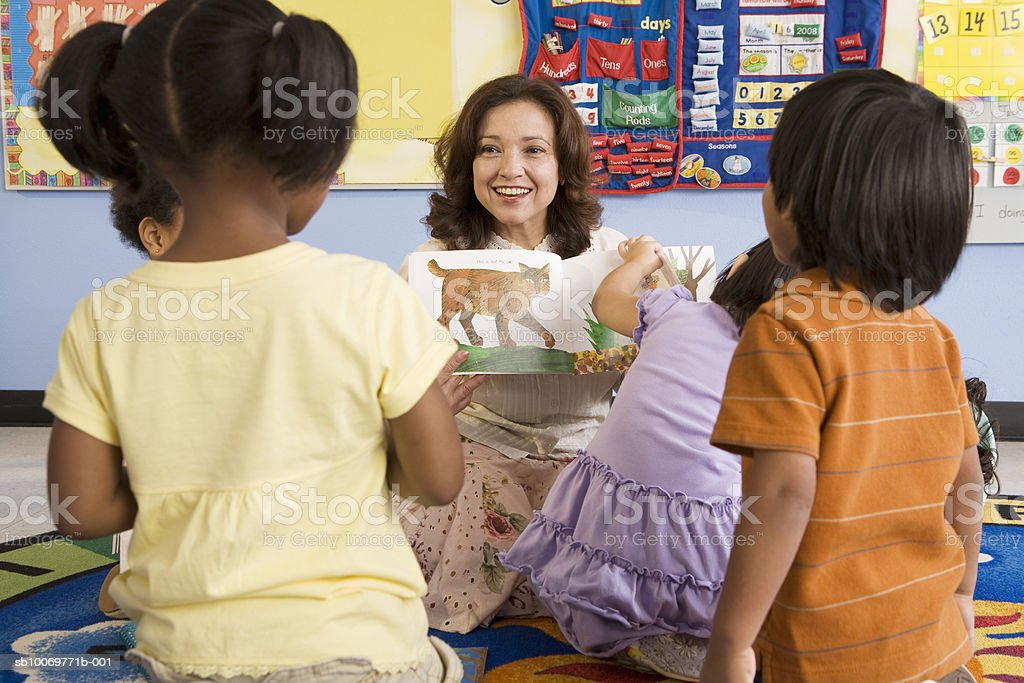 Teacher reading book in classroom royalty-free stock photo