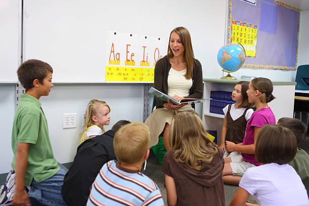lehrer liest ein buch in der klasse - grundschule stock-fotos und bilder