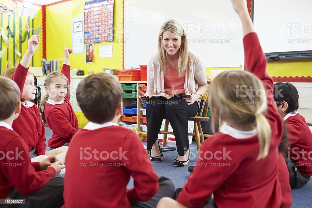 Teacher Reading Story To Elementary School Pupils stock photo
