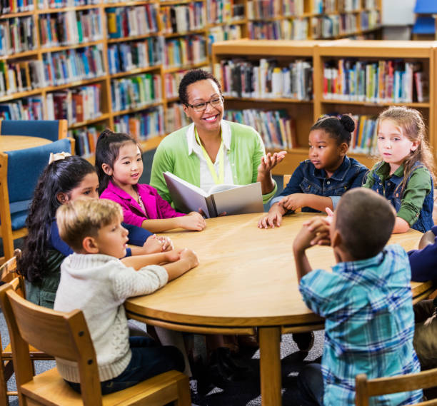 Teacher reading to children in library stock photo