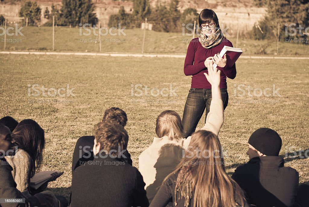 Teacher Reading to her students on lawn royalty-free stock photo