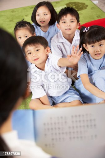 181085327 istock photo Teacher Reading To Students In Chinese School Classroom 178397838