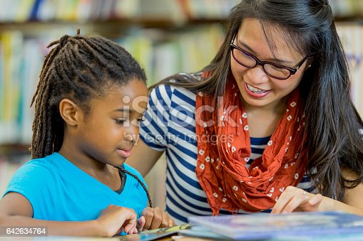 istock Teacher Reading with a Student 642634764
