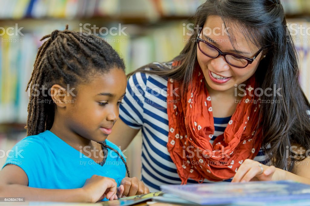 Teacher Reading with a Student stock photo