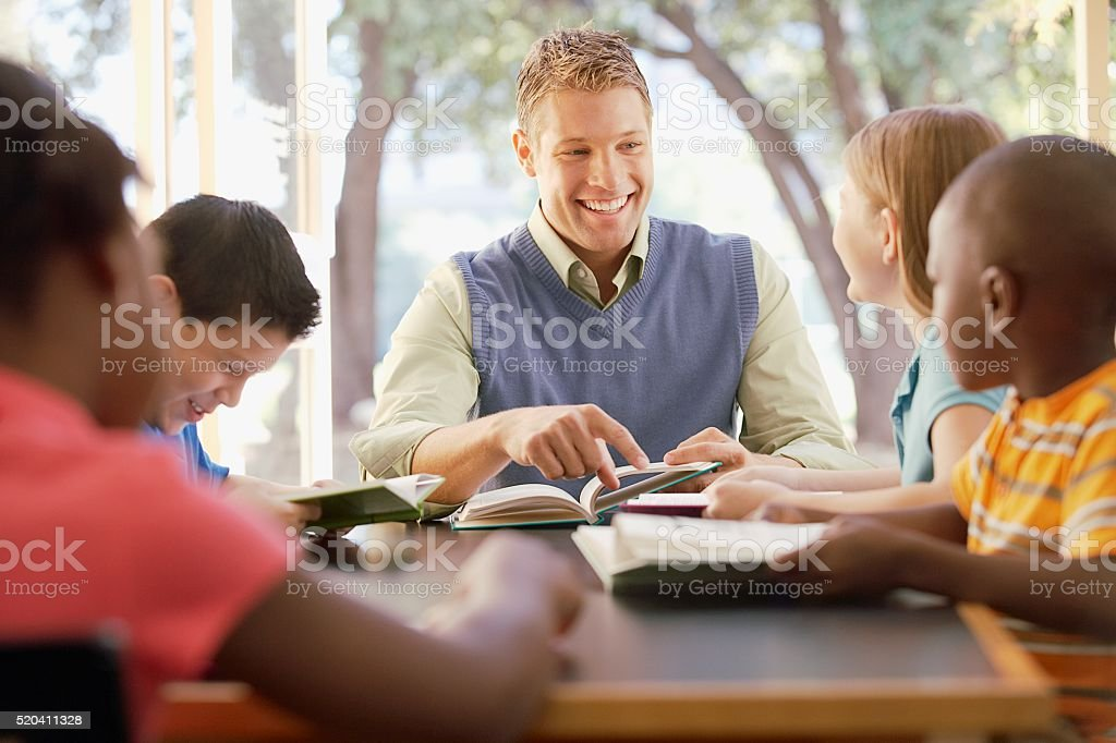 Teacher reading with his class stock photo