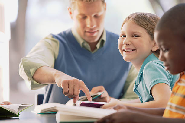 Teacher reading with students stock photo