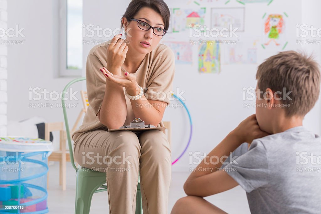 Teacher reprimanding misbehaved child stock photo