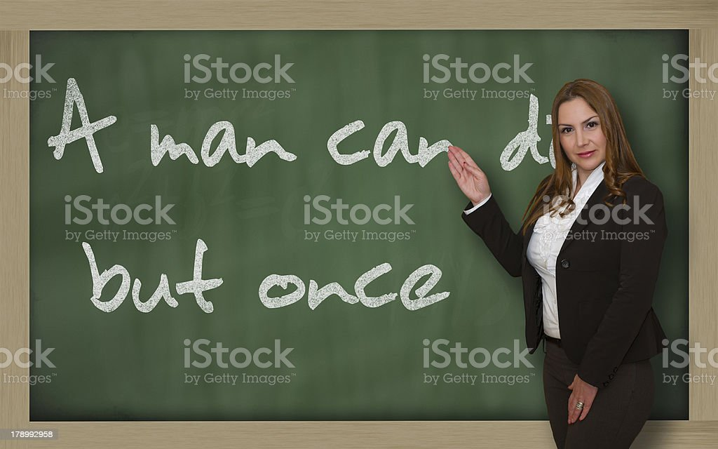 Teacher showing A man can die but once on blackboard stock photo