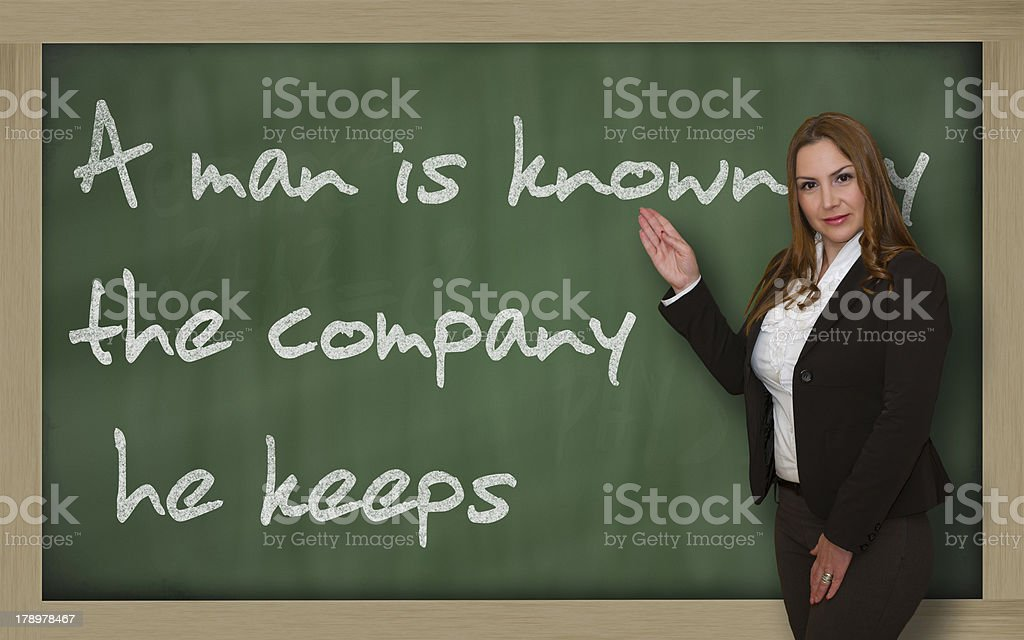 Teacher showing A man is known by the company stock photo