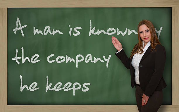 Teacher showing A man is known by the company Successful, beautiful and confident woman showing A man is known by the company he keeps on blackboard known gas stock pictures, royalty-free photos & images