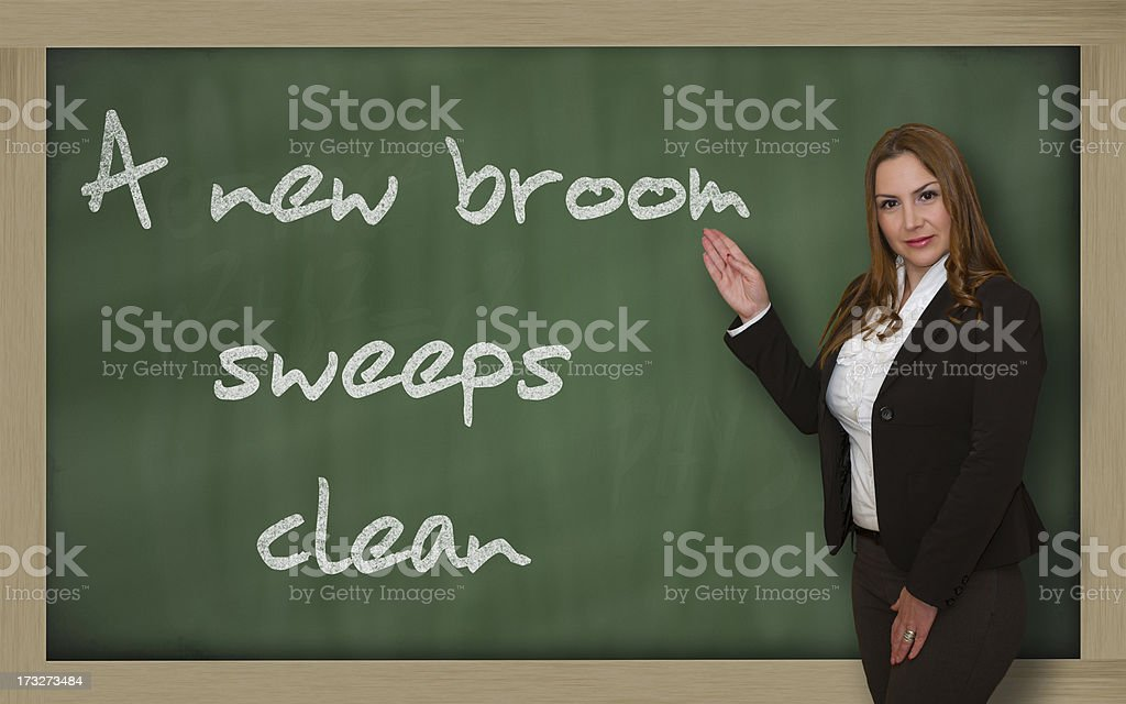 Teacher showing A new broom sweeps clean on blackboard stock photo