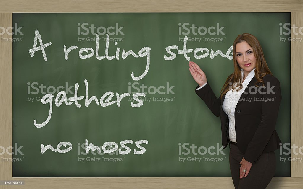 Teacher showing A rolling stone gathers no moss on blackboard stock photo